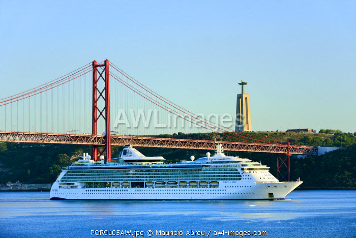 A cruise ship in the Tagus river, leaving the port of Lisbon, passes beneath the 25 de Abril bridge. Christ the King (Cristo Rei) on the background. Lisbon, Portugal