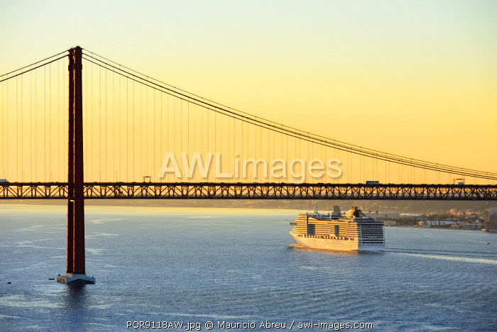 A cruise ship in the Tagus river, leaving the port of Lisbon, passes beneath the 25 de Abril bridge. Portugal