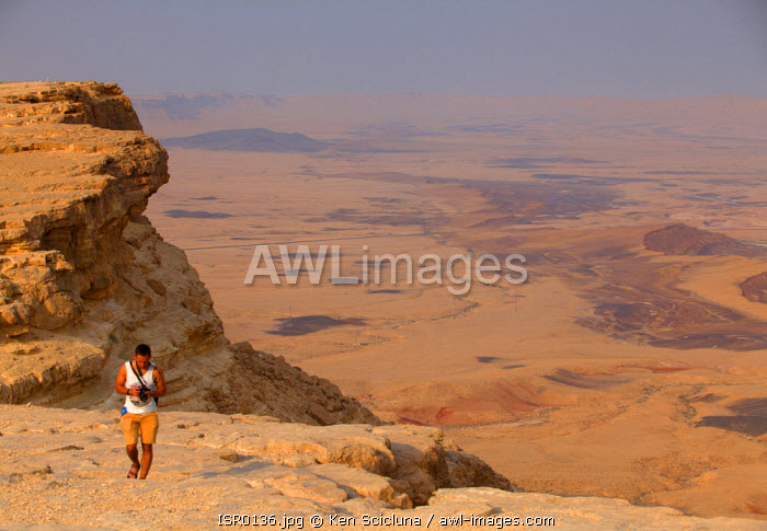 Israel, Negev Desert, Mitzpe Ramon. Man walking at the spectacular Negev desert crater of Makhtesh Ramon in Israel s largest national park the Ramon Nature Reserve.