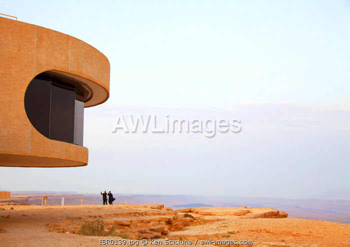 Israel, Negev Desert, Mitzpe Ramon. The Mitzpe Ramon visitor s centre looking like something out of a sci fi movie with the spectacular crater and two Jewish man in the background.