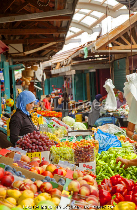Israel, Akko. Muslim woman selling vegetables and fruits from a stall in the market. Unesco.