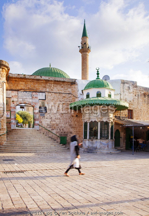 Israel, Akko. Muslim woman walking in front of the entrance to the El Jezzar Pasha Mosque with the green domed sabil on the side. Unesco.