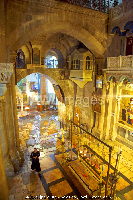 Israel, Jerusalem. View over the stone of unction at the church of the Holy Sepulchre with a believer walking through. Unesco.