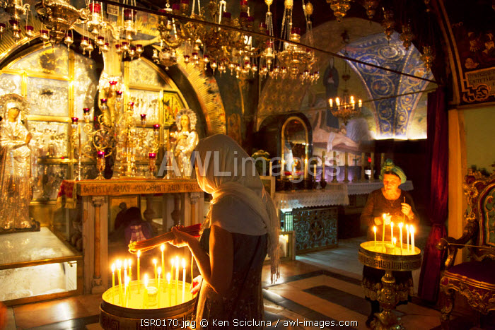 Israel, Jerusalem. Believers lighting a candle at the Chapel of Calvary. Unesco.