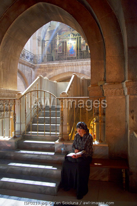 Israel, Jerusalem. Woman reading through a religious book at the Chapel of Calvary at the Church of the Holy Sepulchre. Unesco.