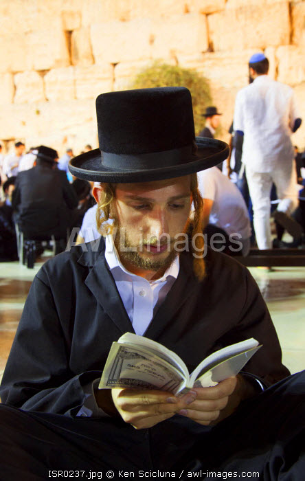 Israel, Jerusalem. Young Orthodox Jew praying at the Western Wall for the destruction of the Holy Temple and launch into exile during the Tisha B'Av final day or 9 Av which is the most intense with Jews sleeping the night out under the stars near the wall. Unesco.