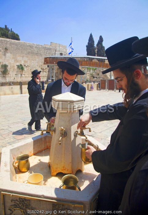 Israel, Jerusalem. Jews washing their hands before entering for mourning and praying at the Western Wall for the destruction of the Holy Temple and launch into exile during the Tisha B'Av final day or 9 Av which is the most intense with Jews sleeping the night out under the stars near the wall. Unesco.