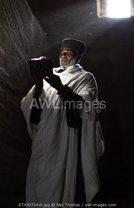 Priest reads his bible in the light from the rock hewn churches window, Ethiopia, Africa