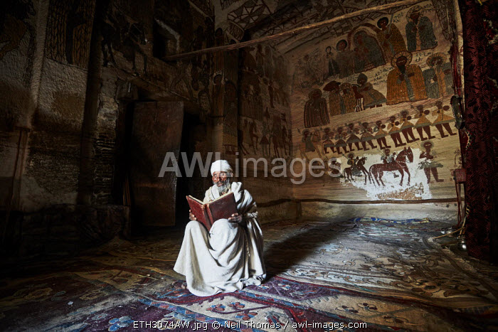 Priest reads his bible in the quiet of the church, Ethiopia, Africa