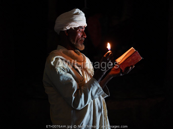 Tigraen priest reads his bible by the light of a candle, Ethiopia, Africa