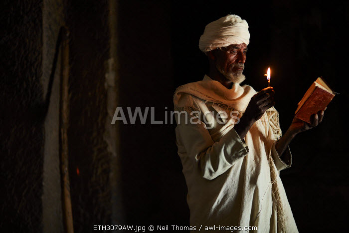 Priest reads his bible in the light of a candle, Ethiopia, Africa