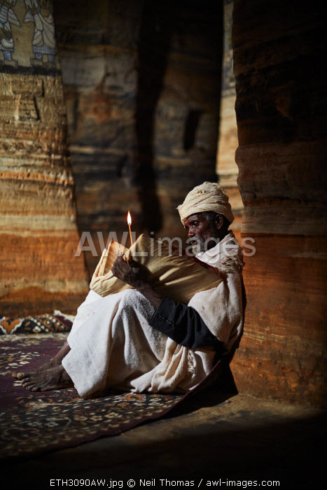Priest reads his bible in the light from the door of the church, Ethiopia, Africa