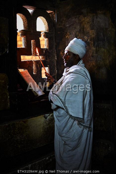 Priest reads his bible in the Yemrehana Kristos Church, Ethiopia, Africa