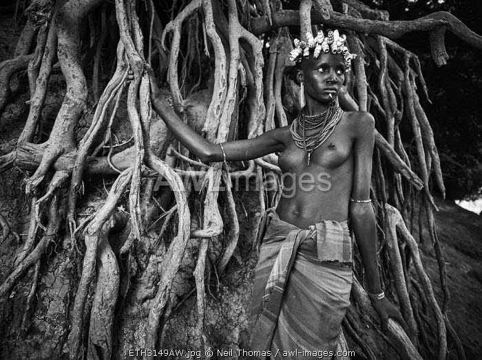 Dassanech woman amoungst some tree routes, Ethiopia, Africa