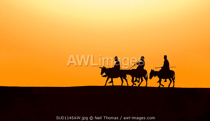 Three Kurmuk men ride their donkeys home in the evening, South Sudan, Africa.