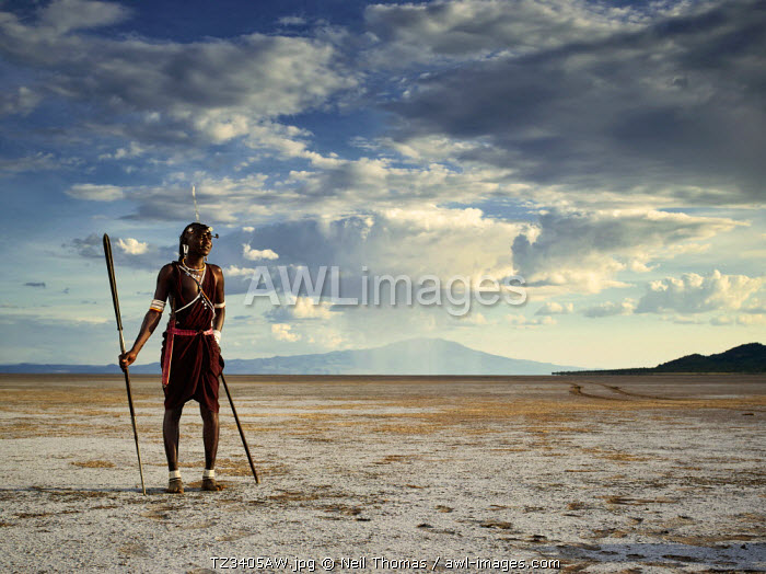 Maasai warrior standing on the dry lakebed of Lake Natron, Tanzania, Africa
