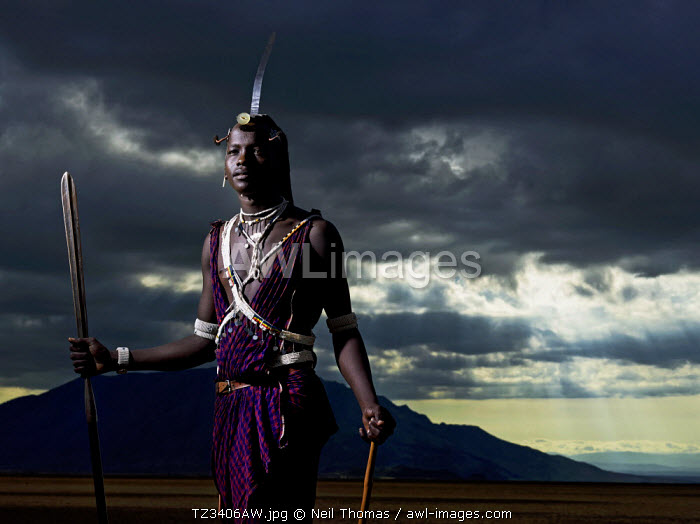 Maasai warrior standing at dusk on the slat flats of lake Natron  with Shompole mountain in the background, Tanzania, Africa