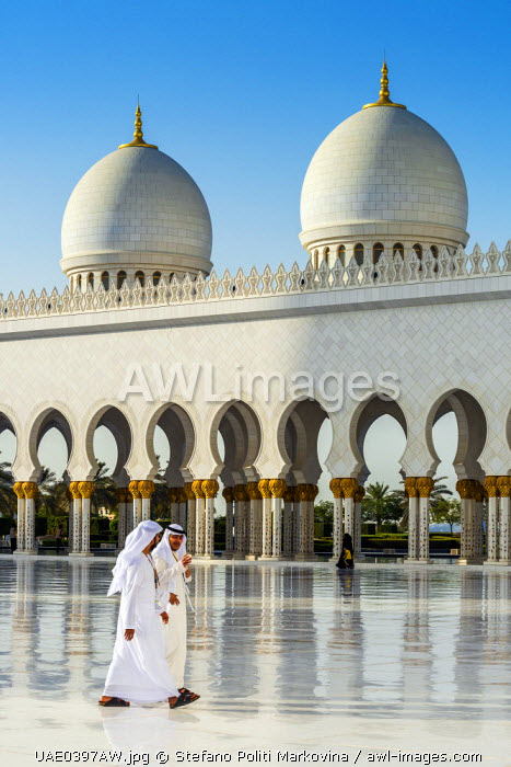 Two Middle Eastern men traditionally dressed walking in the courtyard of the Sheikh Zayed Mosque, Abu Dhabi, United Arab Emirates
