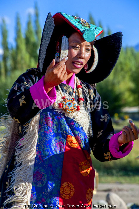 India, Jammu & Kashmir, Ladakh. A Ladakhi woman wears traditional clothes including a turquoise-studded headdress, or perak, and a ceremonial brocade mantle or shawl.