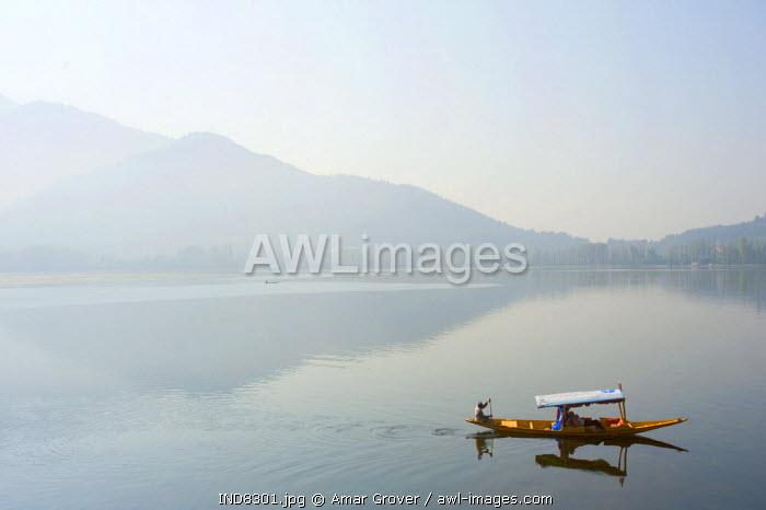 India, Jammu & Kashmir, Kashmir, Srinagar. Tourists enjoy Srinagar's celebrated Dal Lake and its Zabarwan Hills backdrop from the comfort of a shikara - small wooden boats still widely used for transport and tourism.