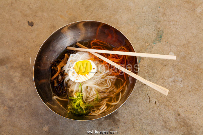 Cold Noodle Soup is a traditional and very popular dish consisting of long, thin handmade noodles in a broth, often topped with a boiled egg, North Korea