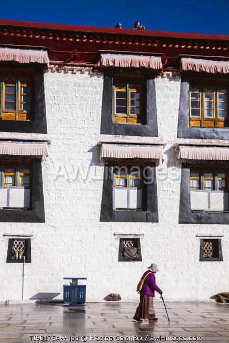 Pilgrim with traditional dress walking in Barkhor square, Lhasa, Tibet, China