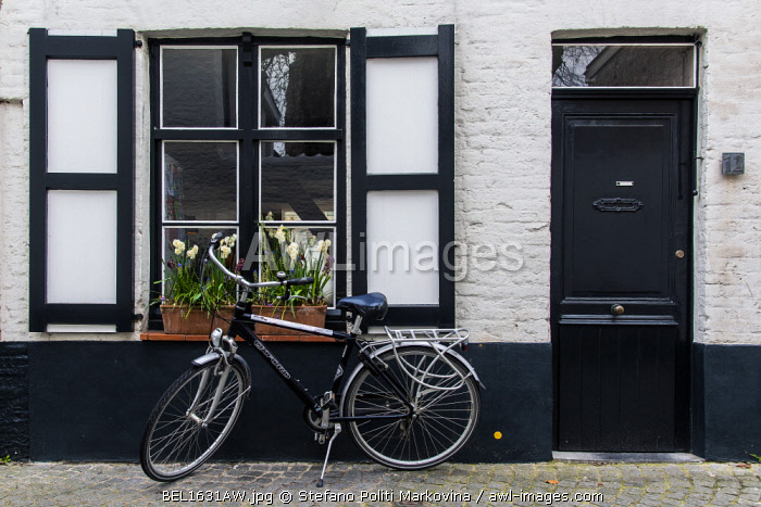 Cobbled street with parked bicycle in the old town, Bruges, West Flanders, Belgium