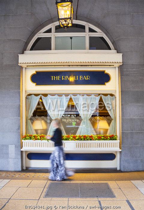 United Kingdom. England. London. Stylish woman walking in front of the Ritz luxury bar window.