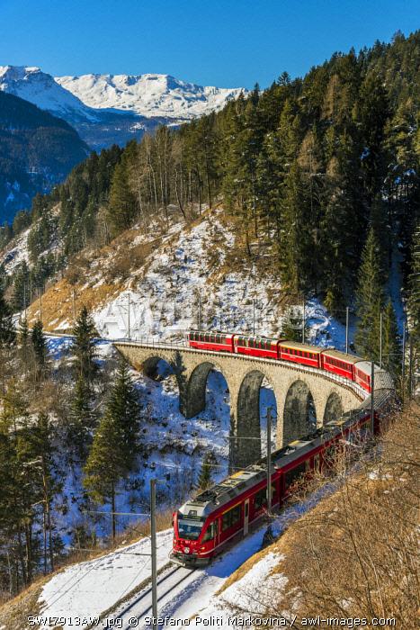 The famous red train of Albula mountain railway passing through a scenic winter alpine landscape near Filisur, Graubunden, Switzerland