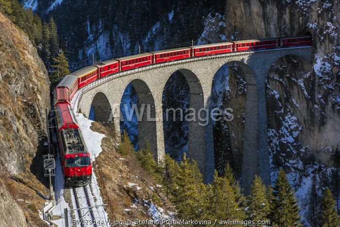 The famous red train of Albula mountain railway while passing on the Landwasser viaduct near Filisur, Graubunden, Switzerland
