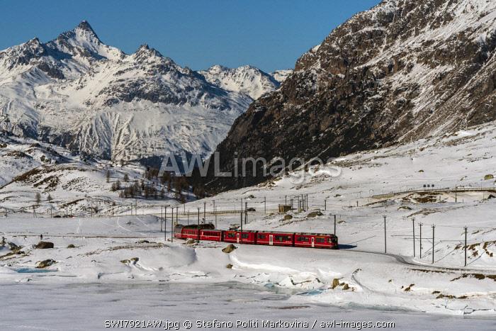 The famous Bernina Express red train passing Lago Bianco in a scenic winter mountain landscape, Graubunden, Switzerland