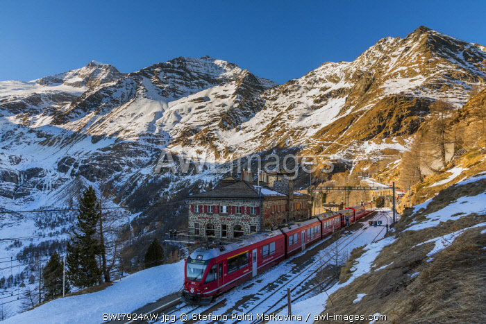 The famous Bernina Express red train at Alp Grum station in a scenic winter day, Graubunden, Switzerland