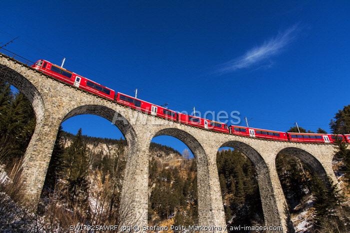 The famous red train of Albula mountain railway while passing on the Landwasser viaduct near Filisur, Graubunden, Switzerland