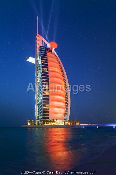The luxury 7 Star Burj Al Arab Hotel designed by the architects Atkins, floodlit at twilight, Um Suqaim Second, Dubai, Dubayy, United Arab Emirates.