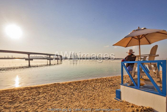 A lifeguard keeps watch on the Beach of the 5 star luxury Atlantis Resort Hotel, looking out over the Palm Jumeriah Lagoon, the Palm Atlantis Monorail and  looking towards Dubai Marina, The Palm Jumeriah, Dubai, United Arab Emirates.