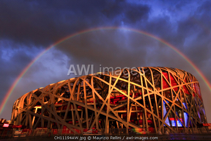 China, Beijing, Olympic park and famous bird's nest stadium made of steel illuminated by a colorful sunset with a rainbow