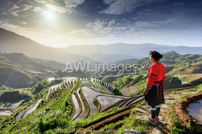 China, Guangxi Province, Longsheng, a woman from a local ethnic minority famous for their very long hair at Long Ji rice terraces with Tiantou village in the background