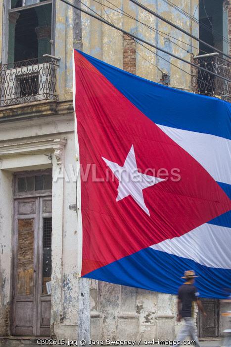 Cuba, Huge Cuban flag hanging across buildings in a street in  Santa Clara, after the death of Fidel Castro