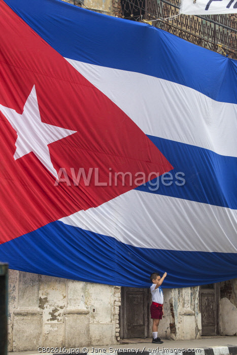 Cuba, Boy saluting to Huge Cuban flag hanging across buildings in a street in  Santa Clara, after the death of Fidel Castro
