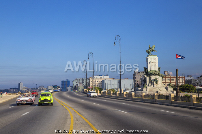 Cuba, Havana, Malecon, Classic American cars passing by Monument to Lieutenant-General Antonio Maceo, known as the �Bronze Titan' and hero of the Wars of Liberation.