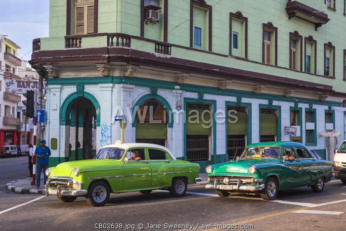 Cuba, Havana, Classic American cars passing by Bar San Juan