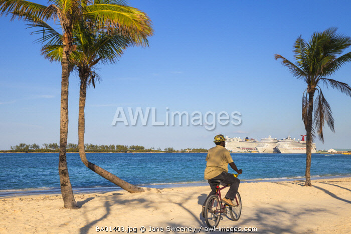Caribbean, Bahamas, Providence Island, Nassau, Man cycling past palm trees on white sand beach, with cruise ship in distance