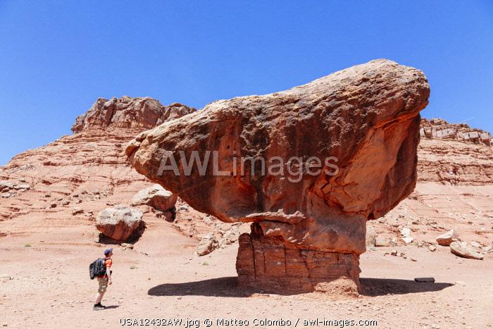 Man standing under big rock, Utah, USA