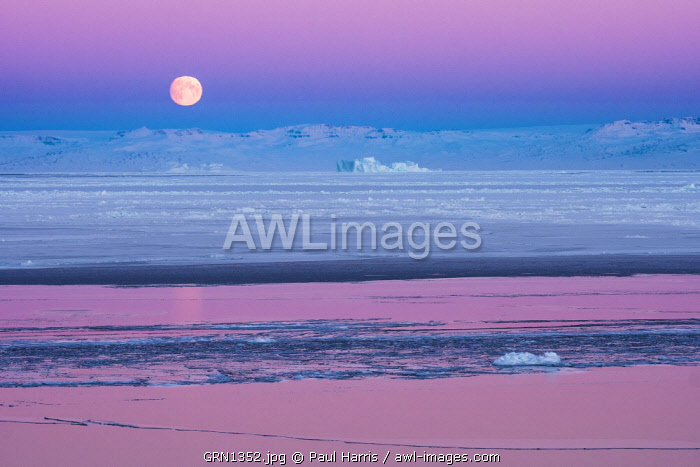 Moon set and sunrise over the Inuit settlement of Oqaatsut, West Greenland
