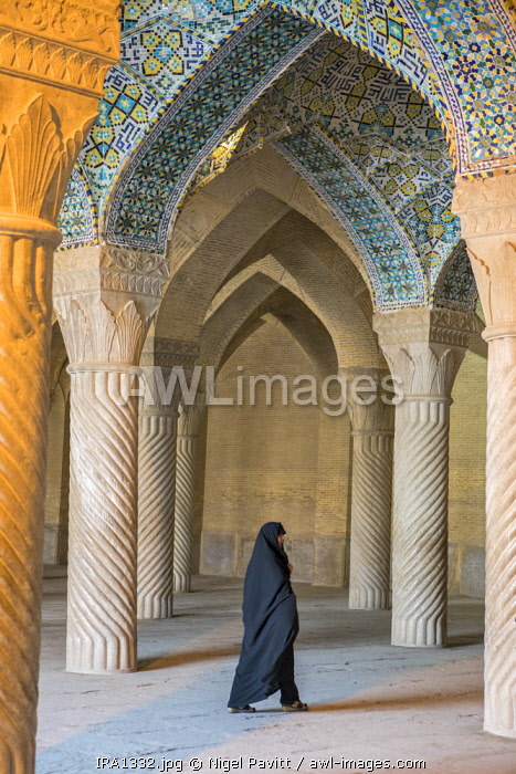 Iran, Shiraz. A woman walks through the prayer hall of the Vakil Mosque with its vaulted brick ceiling and beautifully carved columns.