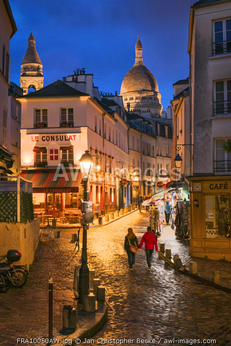 Tourist couple walking along the streets of Montmartre at night with illuminated Sacre Coeur Basilica in the background, Paris, France