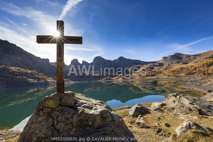 France, Alpes de Haute Provence, Parc National du Mercantour (National park of Mercantour), Haut Verdon, wooden cross by the lake of Allos (2 228m) in autumn, in the background of impressive towers of stoneware of Annot
