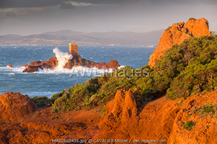 France, Var, Saint Raphael, heavy swell and high winds on the red cliffs of volcanic origin (rhyolite) of the Cap du Dramont, in background the tower of the ile d'Or