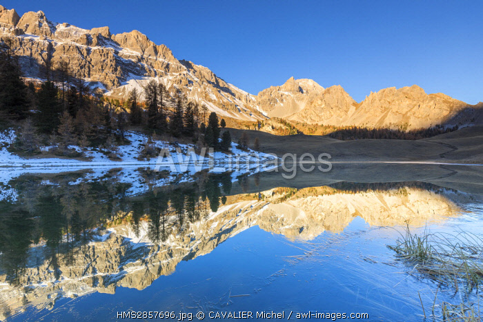 France, Hautes Alpes, regional natural reserve of Queyras, Ceillac, lake des pres Soubeyrand or lake Mirror (2214m), the sun illuminates the Crete of Veyres (3000m), and to the right the Point of Saume (3043m)