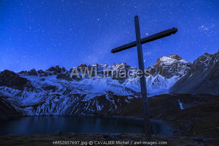 France, Hautes Alpes, regional natural reserve of Queyras, Ceillac, cross of the chapel saint Anne and the lake saint Anne (2415m) dominated by the Peaks of Font Sancte (3385m)